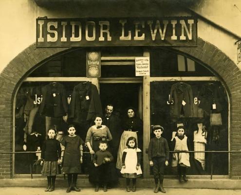 איזידור וג׳ני לוין עם ילדיהם מחוץ לחנות שלהם בהאופטשטראסה (Hauptstrasse) 4, מוגילנו. משמאל: רוזה, פולה, אמה, זיגפריד, מארי, ולטר, פרידה (חסרים: תרזה, הרמן). התמונה צולמה בסביבות 1913.